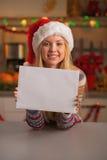 Adolescente feliz en el sombrero de santa que muestra la hoja del papel en blanco Imagenes de archivo