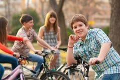 Adolescente feliz en la bicicleta con los amigos Imágenes de archivo libres de regalías