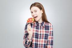Adolescente feliz en la camisa de tela escocesa que coloca y que come la piruleta Imagen de archivo