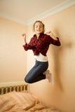 Adolescente feliz en la camisa que salta en cama Imagen de archivo