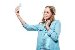 Adolescente feliz en las lentes que toman el selfie con smartphone aislado en blanco Imagen de archivo