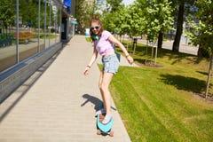 Adolescente feliz en las sombras que montan en longboard Imagenes de archivo