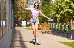 Adolescente feliz en las sombras que montan en longboard Fotografía de archivo libre de regalías