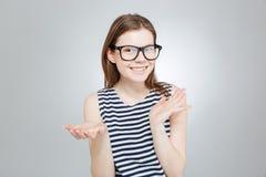 Adolescente feliz en los vidrios que llevan a cabo el copyspace en ambas palmas Fotos de archivo libres de regalías