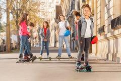 Adolescente feliz en pcteres de ruedas con los amigos Imagen de archivo libre de regalías