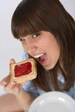 Adolescente feliz en pijamas que come la tostada sana Imágenes de archivo libres de regalías