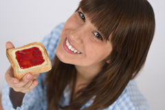 Adolescente feliz en pijamas que come la tostada sana Imagen de archivo libre de regalías