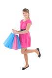 Adolescente feliz en rosa con los bolsos de compras Foto de archivo libre de regalías