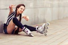 Adolescente feliz en sentarse rollerblading en la calle Imagen de archivo