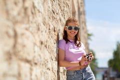 Adolescente feliz en sombras con la cámara en la calle Foto de archivo libre de regalías