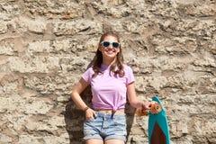 Adolescente feliz en sombras con longboard Fotos de archivo libres de regalías