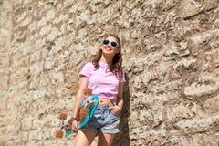 Adolescente feliz en sombras con longboard Fotografía de archivo libre de regalías