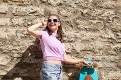 Adolescente feliz en sombras con longboard Imágenes de archivo libres de regalías