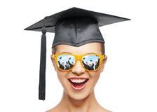 Adolescente feliz en sombras y sombrero del birrete Fotografía de archivo
