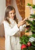 Adolescente feliz en suéter de lana que adorna el árbol de navidad a Imagen de archivo