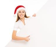 Adolescente feliz en un sombrero de la Navidad que sostiene una bandera grande Fotos de archivo libres de regalías