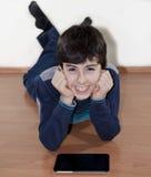 Adolescente feliz está mirando a la libreta de Digitaces Foto de archivo libre de regalías