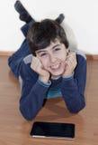 Adolescente feliz está mirando a la libreta de Digitaces Fotografía de archivo