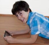 Adolescente feliz está mirando a la libreta de Digitaces Fotografía de archivo libre de regalías