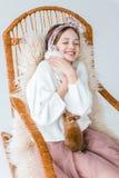 Adolescente feliz hermoso que abraza conejos mientras que se sienta en mecedora Imagen de archivo