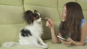 Adolescente feliz hermoso que comunica en smartphone y con su perro Imagen de archivo