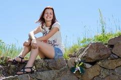 Adolescente feliz hermoso que se sienta en fondo y la sonrisa del cielo azul Imagen de archivo