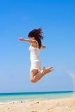 Adolescente feliz joven que salta en la playa. Imagen de archivo