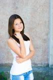 Adolescente feliz joven que se coloca en la pared gris Foto de archivo libre de regalías