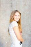 Adolescente feliz joven que se coloca en la pared gris Imágenes de archivo libres de regalías