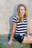 Adolescente feliz joven que se sienta en el copyspace gris del fondo de la pared Fotografía de archivo libre de regalías