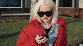 Adolescente feliz joven que usa el teléfono y divirtiéndose en parque de la primavera Estudiante modelo feliz rubio del retrato d metrajes