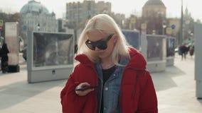 Adolescente feliz joven que usa el teléfono y divirtiéndose en parque de la primavera Estudiante modelo feliz rubio del retrato d almacen de metraje de vídeo