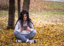 Adolescente feliz joven que usa su tableta y escuchando la música en parque de la ciudad del otoño Imagen de la forma de vida de  Imagen de archivo libre de regalías
