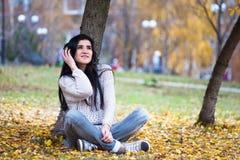 Adolescente feliz joven que usa su tableta y escuchando la música en parque de la ciudad del otoño Imagen de la forma de vida de  Imagenes de archivo