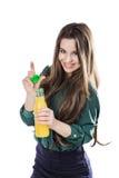 Adolescente feliz mientras que sostiene una botella de zumo de naranja en una blusa verde Aislado en un fondo blanco abre una bot Foto de archivo libre de regalías