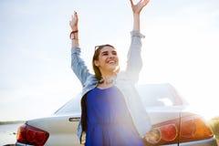 Adolescente feliz o mujer joven cerca del coche Imagenes de archivo