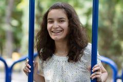Adolescente feliz que balancea en el parque Imagenes de archivo