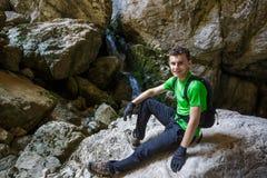 Adolescente feliz que camina cerca de una cascada en una cueva Imagen de archivo libre de regalías