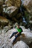Adolescente feliz que camina cerca de una cascada en una cueva Fotografía de archivo