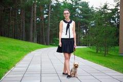 Adolescente feliz que camina con el terrier de Yorkshire del perro en parque Fotografía de archivo libre de regalías
