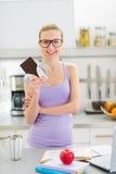Adolescente feliz que come el chocolate mientras que estudia Foto de archivo