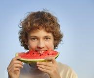 Adolescente feliz que come la sandía Imagenes de archivo