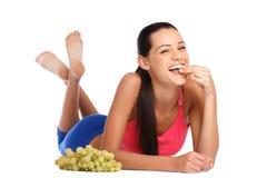 Adolescente feliz que come las uvas aisladas en blanco Imágenes de archivo libres de regalías