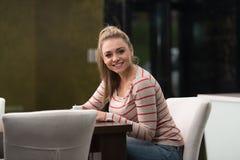 Adolescente feliz que descansa en cafetería Imagen de archivo libre de regalías