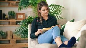 Adolescente feliz que descansa sobre el sofá en la sala de estar mientras que lee su libro nuevo preferido en casa Imágenes de archivo libres de regalías