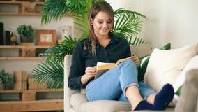 Adolescente feliz que descansa sobre el sofá en la sala de estar mientras que lee su libro nuevo preferido en casa Fotos de archivo