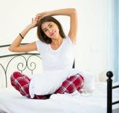 Adolescente feliz que despierta y que sonríe dentro Imagen de archivo