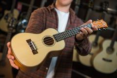 Adolescente feliz que elige la mejor guitarra acústica en tienda musical Fotos de archivo