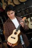Adolescente feliz que elige la mejor guitarra acústica en tienda musical Foto de archivo libre de regalías