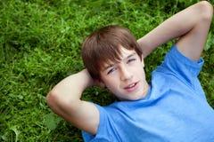 Adolescente feliz que encontra-se na grama no parque fotos de stock